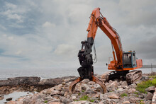 Red Excavator With Rock Or Stone Grab Attached To The Arm. Heavy Machinery Equipment On A Construction Site By The Ocean