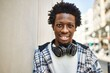 Handsome black man with afro hair wearing headphones smiling happy outdoors
