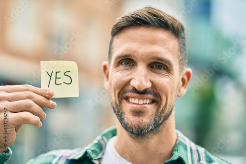 Fotomural Young caucasian man smiling happy holding yes reminder papaer at the city
