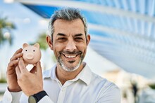 Middle Age Grey-haired Man Smiling Happy Holding Piggy Bank At The City.