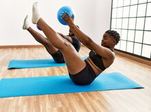 Young African American Sporty Couple Training Pilates Using Ball At Sport Center.