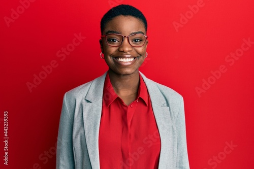 Tablou Canvas Young african american woman wearing business jacket and glasses with a happy and cool smile on face