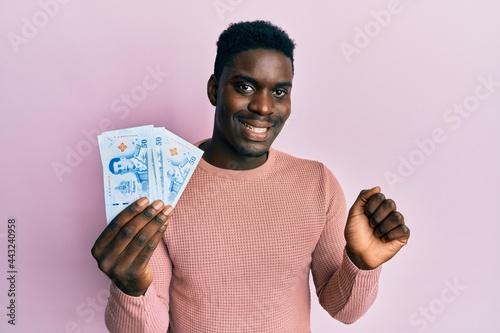 Fotografia, Obraz Handsome black man holding 50 thai baht banknotes screaming proud, celebrating v