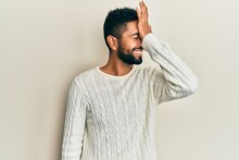 Handsome Hispanic Man With Beard Wearing Casual Winter Sweater Surprised With Hand On Head For Mistake, Remember Error. Forgot, Bad Memory Concept.