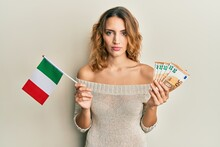 Young Caucasian Woman Holding Italy Flag And Euros Banknotes Relaxed With Serious Expression On Face. Simple And Natural Looking At The Camera.