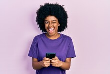 Young African American Woman Using Smartphone Typing Message Winking Looking At The Camera With Sexy Expression, Cheerful And Happy Face.