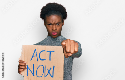 Obraz na plátně Young african american girl holding act now banner pointing with finger to the c