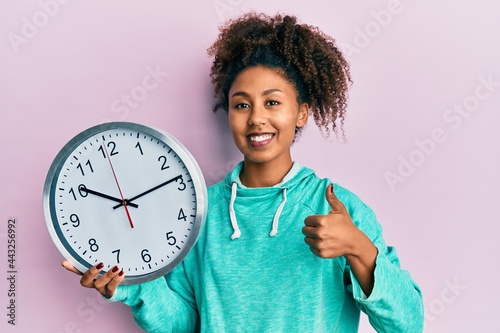 Stampa su Tela Beautiful african american woman with afro hair holding big clock smiling happy