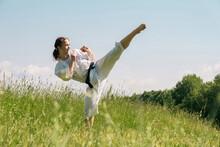 Teen Girl Training Karate Kata Outdoors, Performs The Mawashi Geri Kick