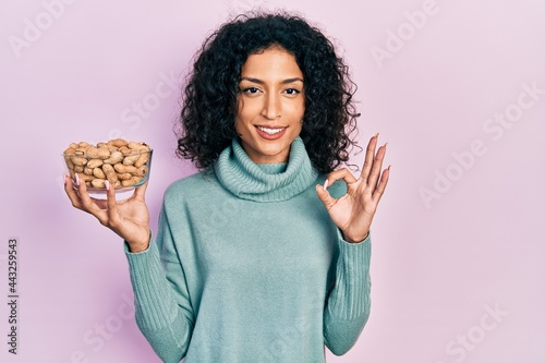 Fotografia Young latin girl holding peanuts doing ok sign with fingers, smiling friendly ge