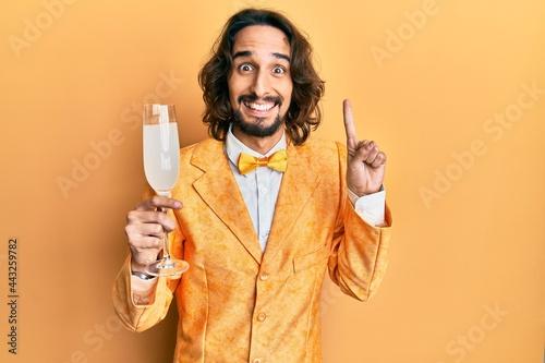 Foto Young hispanic man wearing nerd elegant style drinking a glass of sparkling cham