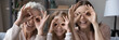 Leinwandbild Motiv Having fun with mommy and granny. Funny family portrait of three women generations older grandmother grownup mother and little daughter look at camera through cute glasses of fingers. Web banner image