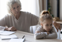 Upbringing Difficulties. Old Lady Teacher Look With Reproach At Disobedient Pupil Girl Turning Away Refusing To Study. Annoyed Older Grandma Talk To Obstinate Grandchild Try To Convince She Is Wrong