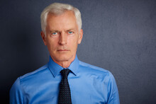 Cropped Shot Of Handsome Elderly Man Wearing Shirt And Tie While Standing With Folded Arms At Dark Grey Background. Senior Man Portrait.