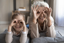 Funny Goggles. Portrait Of Cheerful Little Girl Grandchild Lying On Floor With Senior Granny Playing Having Fun Look At Camera Show Binoculars Glasses Of Fingers. Good Vision And Eye Care For All Ages