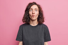 Portrait Of Funny Brunette Woman Makes Fish Face With Lips Comic Grimace Dressed In Casual Black T Shirt Stares Bugged Eyes Has Playful Mood Isolated Over Pink Background. Childish Female Model