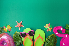Summer Holiday Vacation Concept With Beach Accessories And Tropical Leaves On Green Background