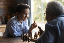 Happy Clever Grandson Beating Grandpa In Chess Battle. Grandfather And Grandkid Playing Chess, Competing In Strategy, Boy Winning And Taking Queen. Strategic Game, Family Activity Concept
