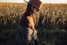 Beautiful Stylish Woman In Brown Hat Walking In Sunset Light In Autumn Field. Atmospheric Moment. Fashionable Young Hipster Female In Retro Outfit Standing At Maize Field In Evening Countryside