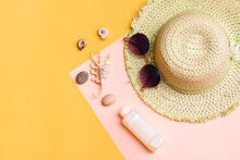 Beach Vacation. A Straw Hat, Sunglasses, A Bottle Of Sunscreen And Shells On A Yellow-pink Cardboard. Items For Sunbathing And Tanning. Top View