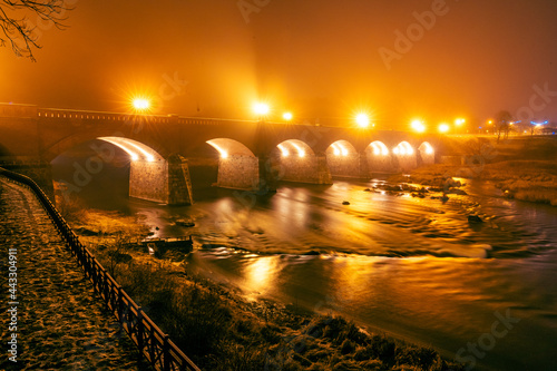 Canvas Print Autumn night view of an old brick bridge built in arches where fog rises from th