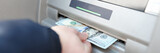 Fototapeta Kawa jest smaczna - Man's hand takes out banknotes from an ATM
