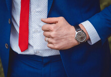 The Hand Of A Man With A Hand Watch Holds On To A Blue Suit Against The Background Of A White Shirt And Red Tie, A Business Men's Style Of Clothing Decor
