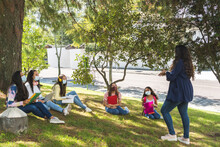 Teacher Teaching Outdoor Classes To A Group Of Latina Teenage Students Wearing A Mask And Social Distancing Due To The Coronavirus Pandemic