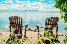 Two Muskoka Chairs By The Water On Home Terrace With Calm View Of Lake In Canada. Summer Cottage Vacation Lifestyle.