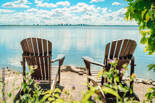 Fototapeta premium Two Muskoka chairs by the water on home terrace with calm view of lake in Canada. Summer cottage vacation lifestyle.