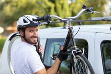 Happy Man Lifting His Bike Off A Car