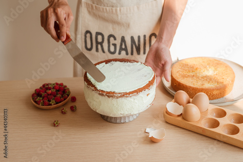 Photo Putting the cream on top of sponge cake