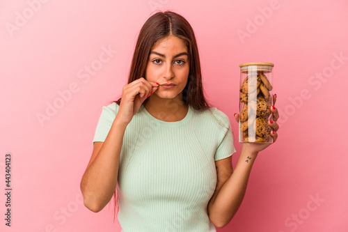 Fotografia Young caucasian woman holding a cookies jar isolated on pink background with fingers on lips keeping a secret