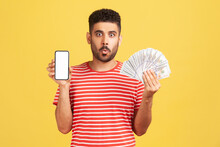 Funny Man With Beard In Red Striped T-shirt Holding In Hands Empty Display Smartphone And Credit Card, Looking At Camera With Surprised Expression. Indoor Studio Shot Isolated On Yellow Background