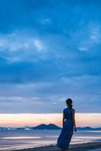 夕暮れの海にいる女性