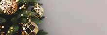 Banner With Gold Christmas Decorations. New Year Baubles In Front Of Gray Background With Copy Space.