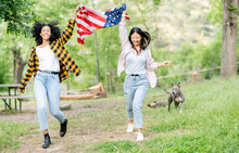 Carefree Multiethnic Couple Of Women Running With American Flag