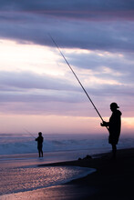 Silhouette Of A Men Fishing On The Seashore At Sunset