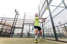 Young Man Playing Paddle Tennis. Low Angle
