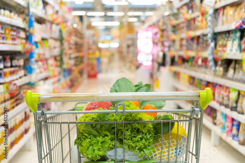 Fototapeta Fresh fruits and vegetables in shopping cart or trolly with aisle and label products on shelves at supermarket or grocery store in mall