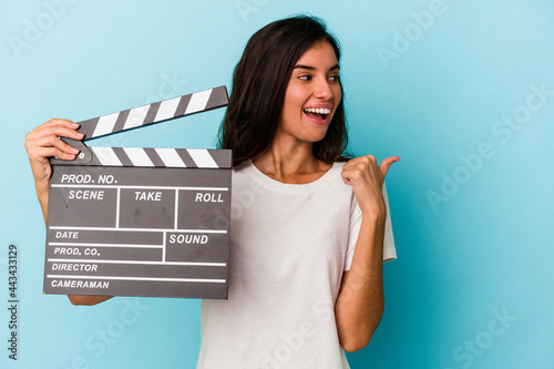 Slika na platnu Young caucasian woman holding a clapperboard isolated on blue background points with thumb finger away, laughing and carefree
