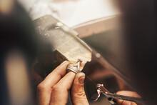 Goldsmith Cutting Metal Piece With Jeweler Saw