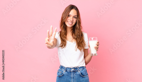 Fotografia young pretty woman smiling and looking friendly, showing number three and holdin
