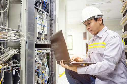 Murais de parede Network administrator holding laptop in hand working Configuration with core swi