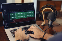 Editing Audio On Laptop Computer With Hands On Keyboard And Headphones, Microphone In Background