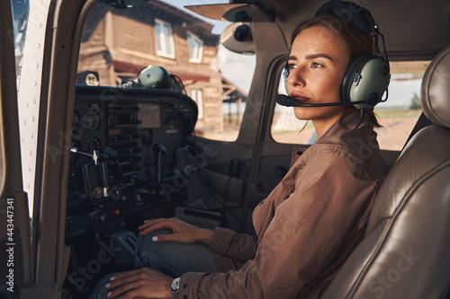 Billede på lærred Attractive young woman sitting inside plane cockpit