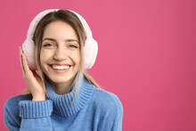 Happy Woman Wearing Warm Earmuffs On Pink Background, Space For Text