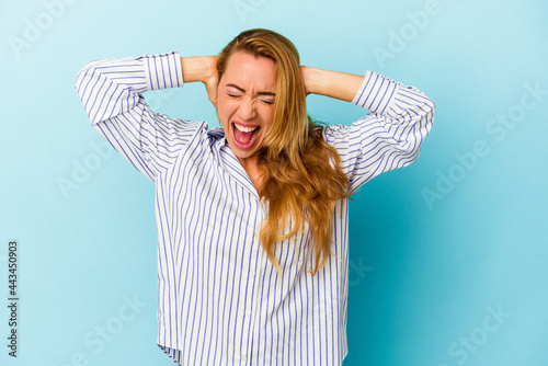 Caucasian woman isolated on blue background covering ears with hands trying not to hear too loud sound Fototapet