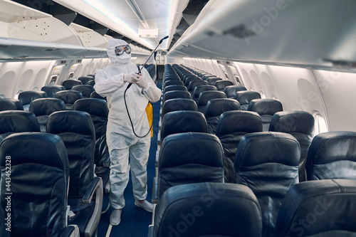 Photo Man doing the antiviral disinfection aboard the plane