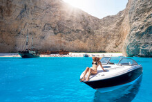 Attractive, Blonde Woman In A Bikini Sits On A Boat Enjoys The Turquoise Sea Of The Famous Shipwreck Beach, Navagio, In The Island Of Zakynthos, Greece